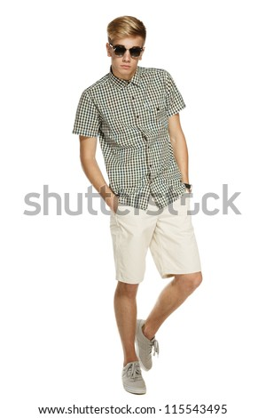 Young handsome male in shorts and sunglasses posing in full length with hands in pockets, over white background - stock photo
