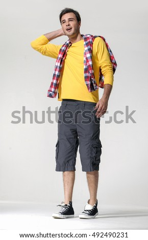 Young handsome male in shorts posing in full length over white background