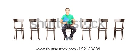 Young handsome male sitting on a chair and waiting for job interview isolated on white background - stock photo