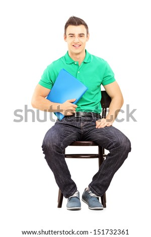 Young handsome male sitting on a chair waiting for job interview isolated on white background - stock photo