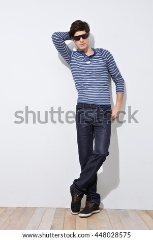 Young handsome male with sunglasses posing in full length over wooden background