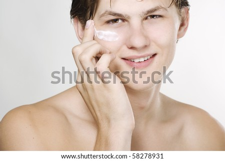 Young handsome man applying cream - stock photo