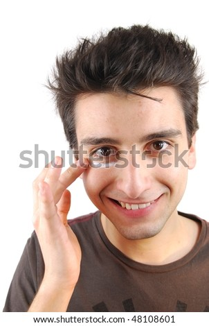 young handsome man applying eye cream (over white background) - stock photo
