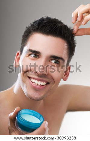 Young handsome man applying hair gel close up - stock photo
