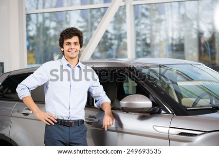 Young handsome man at show room standing near car - stock photo