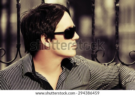 Young handsome man at the cast iron fence - stock photo
