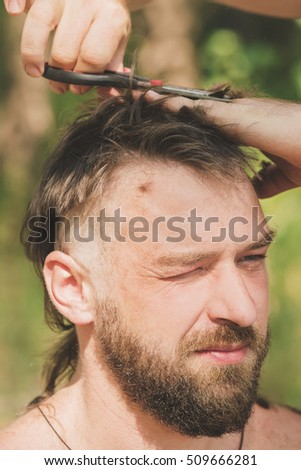 Young handsome man at the time of hair cutting with scissors