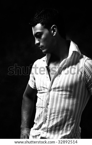 young handsome man black and white portrait, studio shot - stock photo