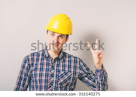 young handsome man builder showing victory sign