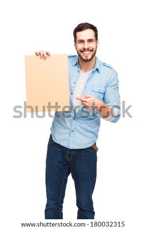 Young handsome man casual dressed smiling and showing a wooden blank panel on white background - stock photo