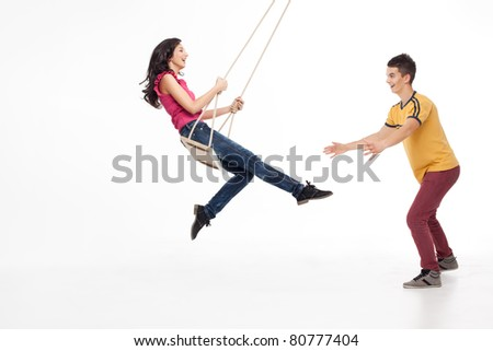 young handsome man catching his swinging girlfriend - stock photo