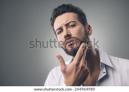 Young handsome man checking his face skin and touching his beard - stock photo