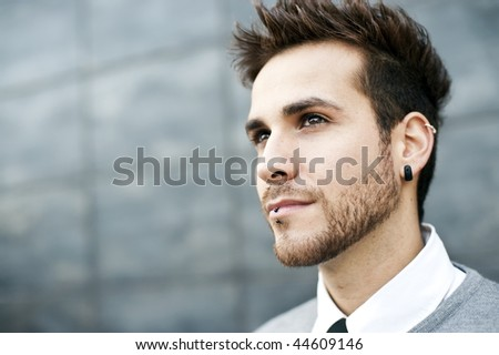 Young handsome man close portrait (piercing in ear and lips) - stock photo