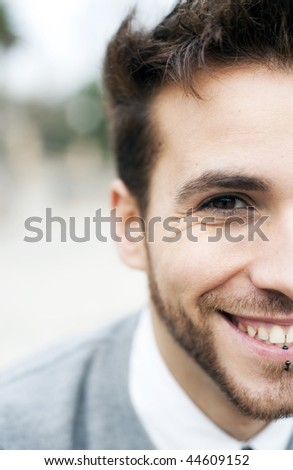Young handsome man close portrait (piercing in his lips, easy to remove) - stock photo