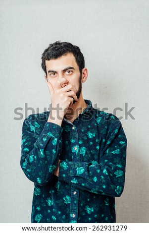 Young handsome man covered her mouth in surprise. Gesture. On a gray background - stock photo