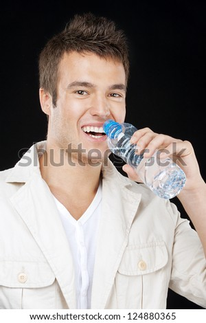 Young handsome man drinks water from bottle, on black background.