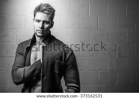 Young handsome man elegant against white brick wall black and white fashion portrait - stock photo
