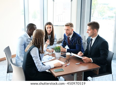 Young handsome man gesturing and discussing something while his coworkers listening to him sitting at the office table - stock photo