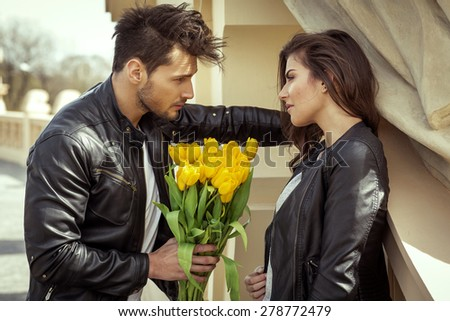 Young handsome man handing flowers - stock photo
