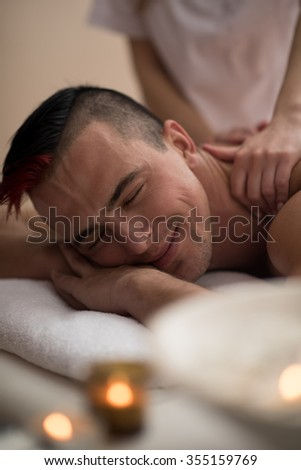 young handsome man have relaxing massage in spa and wellness salon - stock photo