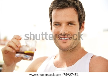 Young handsome man having a drink outdoors - stock photo