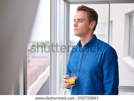 Young handsome man holding a glass of juice and gazing out of a window seemingly lost in deep thought - stock photo