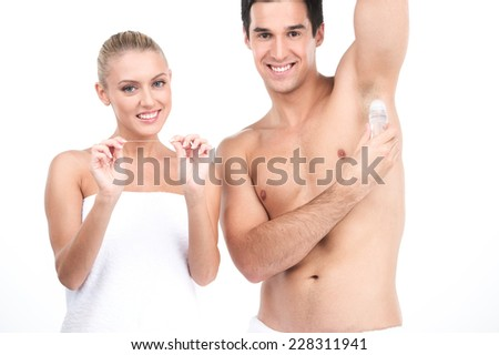 Young handsome man holding deodorant for armpits. beautiful woman standing on white background and holding floss - stock photo