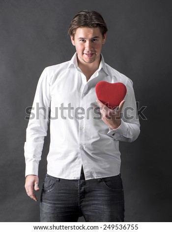 Young handsome man holding red heart on a dark background - stock photo