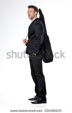 Young handsome man in a dark business suit with guitar