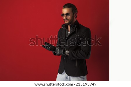 Young handsome man in black coat wears gloves  - stock photo