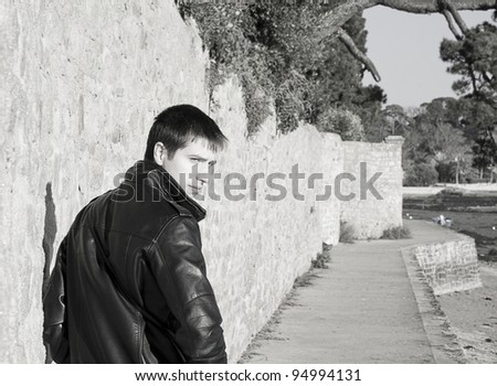Young handsome man in black leather jacket is turning around and looking back seriously - stock photo