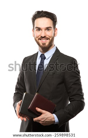 Young handsome man in black suit and business diary isolated on white background - stock photo