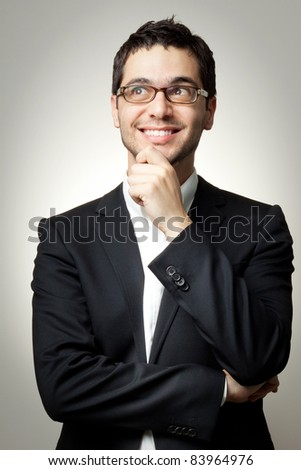 Young handsome man in black suit and glasses looking at copy-space smiling, thinking or dreaming - stock photo