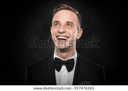 Young handsome man in black suit thinking or dreaming. - stock photo
