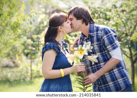 young handsome man in blue shirt with white lily kiss beautiful brunette girl in blue dress in green garden - stock photo