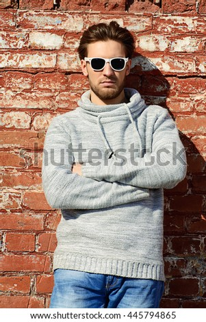 Young handsome man in casual clothes and sunglasses standing on a city street. Men's beauty, fashion. Outdoor portrait. - stock photo