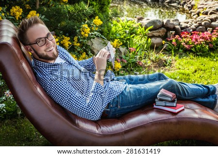 Young handsome man in casual clothes sit in luxury sofa with gift card in summer garden. - stock photo