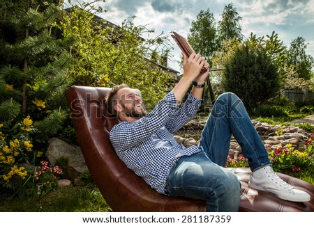 Young handsome man in casual clothes sit in luxury sofa with iPad in summer garden. - stock photo