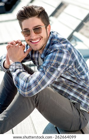 Young handsome man in casual clothes with sunglasses sitting on the wooden sunbed in the city - stock photo