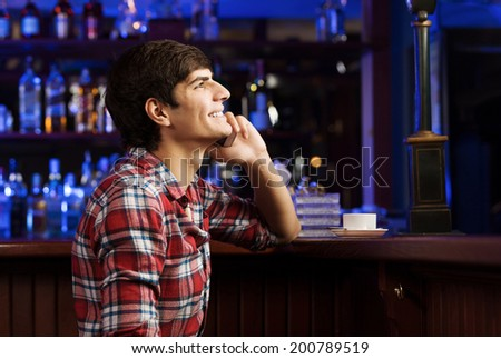 Young handsome man in casual sitting at bar and talking on phone