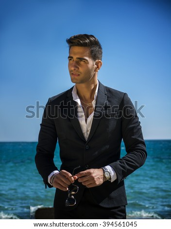 Young handsome man in classical suit on beach holding sunglasses while looking away. Sea waves on background - stock photo