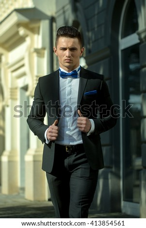 Young handsome man in elegant suit with bow tie stands at glass entrance door