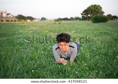 Young handsome man in gray t-shirt and jeans on the green lawn in green sunny spring park. Happy smiling boy resting on the grass.