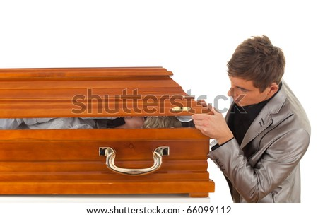 young handsome man in grey suit with coffin - stock photo