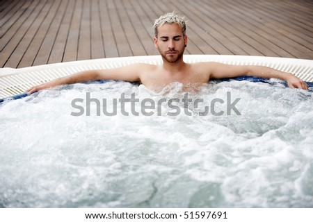 Young handsome man in indoor jacuzzi - stock photo