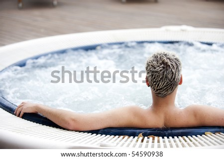 Young handsome man in indoor jacuzzi