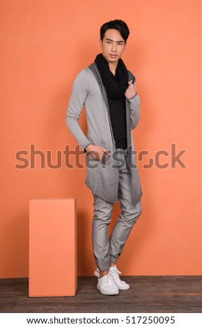 young handsome man in long stylish coat with cube on wooden-orange background