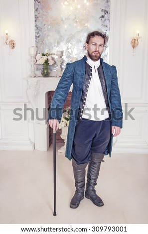 Young handsome man in medieval clothes standing in the room - stock photo