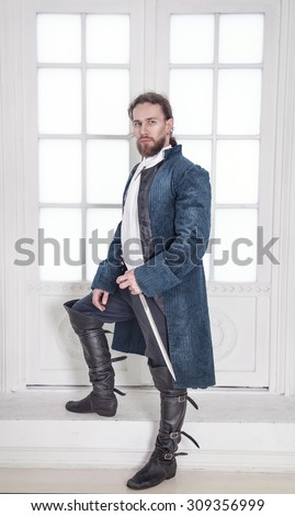 Young handsome man in medieval clothes with sword standing in the room  - stock photo