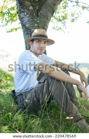 Young handsome man in nature sitting under the tree - stock photo
